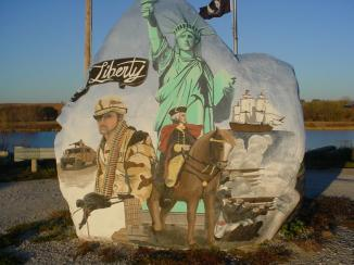 """Freedom Rock November 2006 ~  The Freedom Rock (established in 1999) is a large (approx. 60+ ton) boulder located in rural Iowa that is repainted every year with a different Thank You for our nations Veterans to honor their service to our country.  The artist, Ray """"Bubba"""" Sorensen II, was inspired by the movie Saving Private Ryan, as well as, wanting to give Veterans a unique recognition on Memorial Day.   Sorensen paints The Freedom Rock on his own with the tremendous support of family and friends.  Sorensen is not commissioned to paint the rock but is able to do so each year with the generous help of donations.   While painting murals across the ..."""