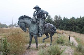 """Trail Boss ~  This is a statue of a Trail Boss on his horse, located in Boot Hill Cemetery, Ogallala Nebraska.     In the stirring days of the late 1800s, when the present city of Ogallala was an infant town on the Union Pacific Railroad, Boot Hill Cemetery was the final resting place for cowboys, drifters, and settlers. Numerous stories are told of those days when gun battles took their toll on human life. Many buried at Boot Hill ran afoul of the law and the streets of Ogallala echoed with gunfire as some slick gambler or horse thief met his end.  One burial was that of """"Rattlesnake Ed,"""" who was shot down over a nine dollar bet in a Monte game in the """"Cowb..."""