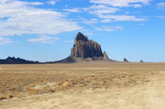 """Shiprock ~  Shiprock (Navajo: Tsé Bit'a'í, """"rock with wings"""" or """"winged rock"""") is a monadnock rising nearly 1,583 feet (482.5 m) above the high-desert plain of the Navajo Nation in San Juan County, New Mexico, United States. Its peak elevation is 7,177 feet (2,187.5 m) above sea level. It lies about 10.75 miles (17.30 km) southwest of the town of Shiprock, which is named for the peak.   Governed by the Navajo Nation, the formation is in the Four Corners region and plays a significant role in Navajo religion, myth, and tradition. It is located in the center of the area occupied by the Ancient Pueblo People, a prehistoric Native American cultur..."""