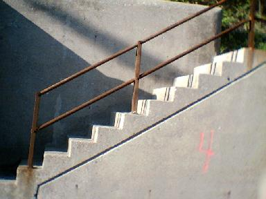 One of a number of staircases built into, not over, a concrete retaining wall.
