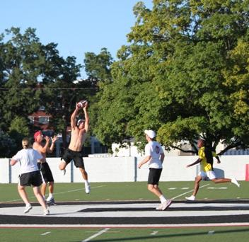 John Isner takes time out to play touch football with some junior tennis players.