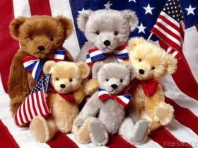 Picture of cute Teddy bears sitting a flag.