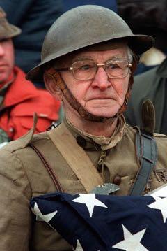 A Veteran from World War I holding a flag.