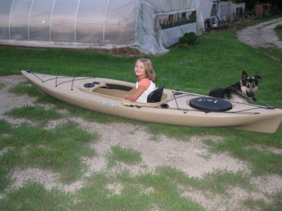 Leah sits in her mom's kayak all ready to go. Our German Shepherd, Bo, is looking on.