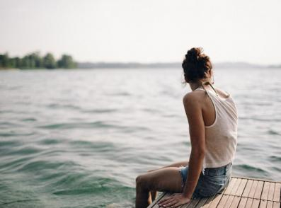 A girl sitting on a pier